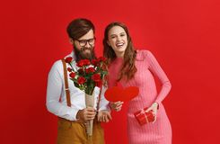 Valentine`s day concept. happy young couple with heart, flowers, gift on red royalty free stock photo