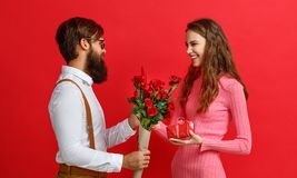 Valentine`s day concept. happy young couple with heart, flowers. Gift on red background stock photos