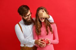 Valentine`s day concept. happy young couple with heart, flowers. Gift on red background royalty free stock images