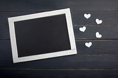 Valentine`s day concept with hearts and chalkboard on the wood background Royalty Free Stock Photography