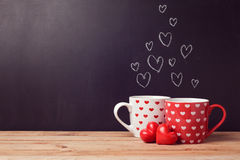 Valentine's day concept with hearts and cups over chalkboard Royalty Free Stock Image