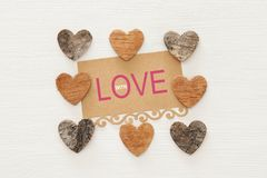 Valentine's day concept. hearts cutted from tree trunk and vintage paper note over wooden white background. Valentine's day concept. hearts cutted stock photo