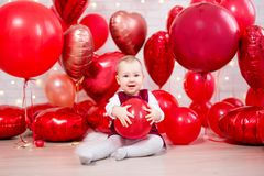 Valentine`s day concept - little baby girl with red balloons. Valentine`s day concept - little baby girl with red heart-shaped balloons royalty free stock image