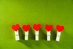 Valentine`s day concept. Red heart shape clothespins with textured green background. Valentine`s day concept. Red heart shape clothespins with textured green Royalty Free Stock Photo