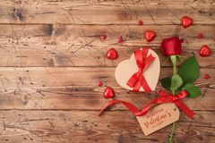 Valentine`s day concept with rose flower, gift box and heart shape chocolate on wooden background. royalty free stock photo
