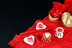 Valentine`s day concept. Teddy bear in heart shaped gift box with candle on black background. Red background royalty free stock photography