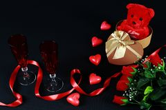 Valentine`s day concept. Teddy bear in heart shaped gift box with candle and red champagne glass on black background. Valentine`s day concept. Teddy bear in stock image