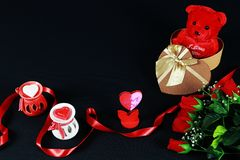 Valentine`s day concept. Teddy bear in heart shaped gift box with candle and red roses on black background. Paper holder royalty free stock photo