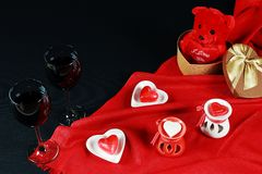 Valentine`s day concept. Teddy bear in heart shaped gift box with candle and red wine on black background. Red background royalty free stock photography
