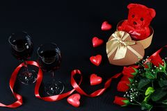 Valentine`s day concept. Teddy bear in heart shaped gift box with candle and red wine on black background. Valentine`s day concept. Teddy bear in heart shaped stock photography