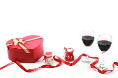 Valentine`s day concept. Two glasses of red wine with heart shaped candle and gift box with red ribbon on isolated white backgroun. D. Valentines day concept royalty free stock images