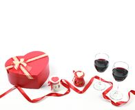 Valentine`s day concept. Two glasses of red wine with heart shaped candle and gift box with red ribbon on isolated white backgroun. D. Valentines day background royalty free stock photo