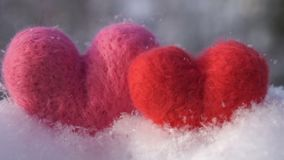 Two Valentine`s woolen hearts on the clear white snow in winter slow motion. Valentine`s day concept two toy hearts made of red and pink wool standing on the stock footage