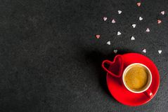 Valentine`s day concept. Coffee mug and sweet heart shaped sprinkles, black background, copy space top view stock images