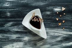 Valentine`s day concept, white cup with coffee on small hearts background and love words on blue wooden texture, natural light, stock images