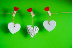 Valentine`s Day concept. White wooden hearts fixed with clothespins on cord on green background Stock Photography