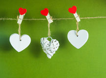 Valentine`s Day concept. White wooden hearts fixed with clothespins on cord on green background Royalty Free Stock Images