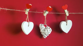 Valentine`s Day concept. White wooden hearts fixed with clothespins on cord on red background stock video footage