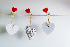 Valentine`s Day concept. White wooden hearts fixed with clothespins on cord on white background Royalty Free Stock Images