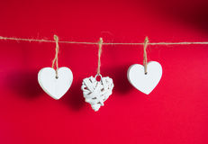 Valentine`s Day concept. White wooden hearts hanging on cord on red background stock photo