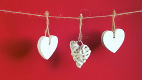 Valentine`s Day concept. White wooden hearts hanging on cord on red background stock footage