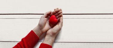 Valentine`s day concept.Woman hands red heart on white table royalty free stock images