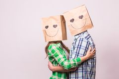Valentine`s day concept - Young love couple with bags over heads on white background.  Stock Photography