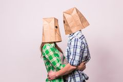 Valentine`s day concept - Young love couple with bags over heads on white background.  Royalty Free Stock Image