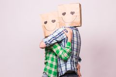 Valentine`s day concept - Young love couple with bags over heads on white background.  Stock Photos