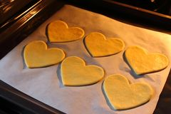 Valentine`s day cookies with heart shape. Baked hearts in oven. Sweet love symbol. Cooking surprise. Romantic biscuit gift. Royalty Free Stock Images