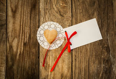 Valentine`s day. Cookies in the shape of a heart on a white napkin and white card on a wooden background Stock Photos