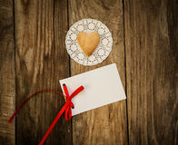 Valentine`s day. Cookies in the shape of a heart on a white napkin and white card on a wooden background Royalty Free Stock Images