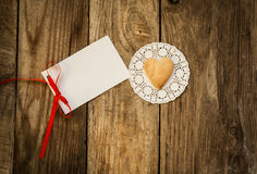 Valentine`s day. Cookies in the shape of a heart on a white napkin and white card on a wooden background Stock Images