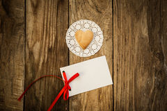 Valentine`s day. Cookies in the shape of a heart on a white napkin and white card on a wooden background Royalty Free Stock Photo