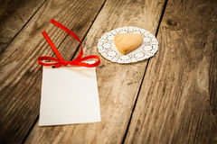 Valentine`s day. Cookies in the shape of a heart on a white napkin and white card on a wooden background, close up Stock Photography