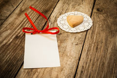 Valentine`s day. Cookies in the shape of a heart on a white napkin and white card on a wooden background, close up Stock Photo