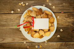 Valentine`s day. Cookies in the shape of a heart on a white plate and white card on a wooden background Stock Photography