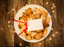 Valentine`s day. Cookies in the shape of a heart on a white plate and white card on a wooden background Royalty Free Stock Photo