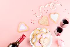 Valentine`s day cookies, wine glasses and wine on pink background. Top view. Valentine`s day cookies, wine glasses and wine on pink background stock photography