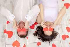 Valentine`s day, a couple in love lies among the hearts on the floor with their eyes closed with hearts