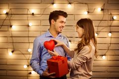 Valentine`s Day couple. St. Valentine`s Day. A loving couple with a gift and a heart Royalty Free Stock Photos