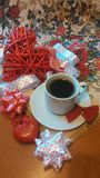Valentine's  day. A cup of black coffee with a figures of a red heart and ribbons on a beautiful napkin with roses Stock Images