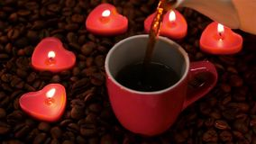 In Valentine`s Day cup of coffee by candlelight. Slow motion stock footage