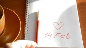 Valentine`s Day Cup of coffee, a notebook with a record of February 14, heart, the rolling marker.  stock footage