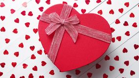 Boxed gift placed on heart shaped red sequins on white wooden table. Valentine`s Day decoration composition. Boxed gift placed on heart shaped red sequins on stock footage
