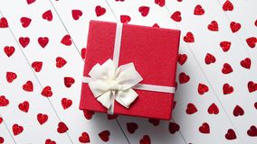 Boxed gift placed on heart shaped red sequins on white wooden table. Valentine`s Day decoration composition. Boxed gift placed on heart shaped red sequins on stock video