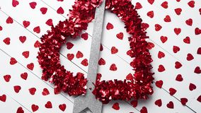 Vlentine`s Day composition. Heart shaped sequins placed on white wooden table. Valentine`s Day decoration composition. Heart with arrow as a love symbol placed stock video footage