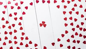 Vlentine`s Day composition. Heart shaped sequins placed on white wooden table. Valentine`s Day decoration composition. Heart shaped red sequins placed on white stock video