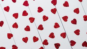 Vlentine`s Day composition. Heart shaped sequins placed on white wooden table. Valentine`s Day decoration composition. Heart shaped red sequins placed on white stock video footage