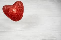 Valentine`s Day. Decoration for the holiday. Burning heart on a white wooden background. Royalty Free Stock Photo